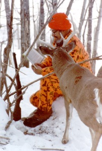 A less cropped version of Dr. Ken Nordberg with a live, wild buck looking over his shoulder.